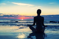 meditation-beach-women-sitting-lotus-38960378